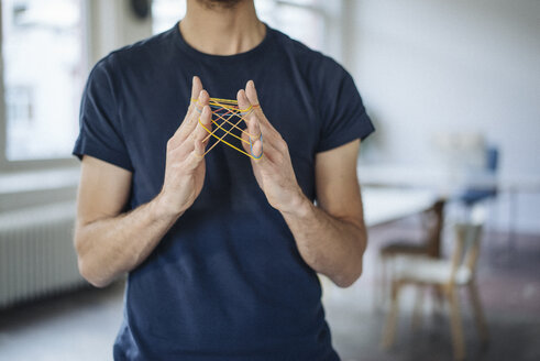 Close-up of man holding rubber bands - KNSF01199