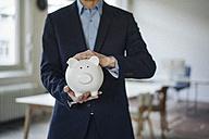 Close-up of businessman holding piggy bank - KNSF01202