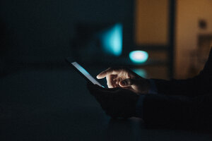 Close-up of businessman working late in office using tablet - KNSF01211