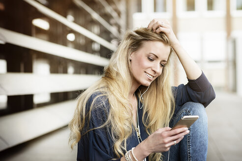 Portrait of smiling blond young woman with earphones looking at cell phone - DMOF00003