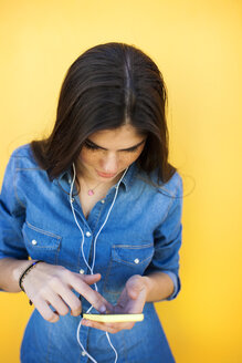 Young woman with earphones and smartphone in front of colourful wall - VABF01285