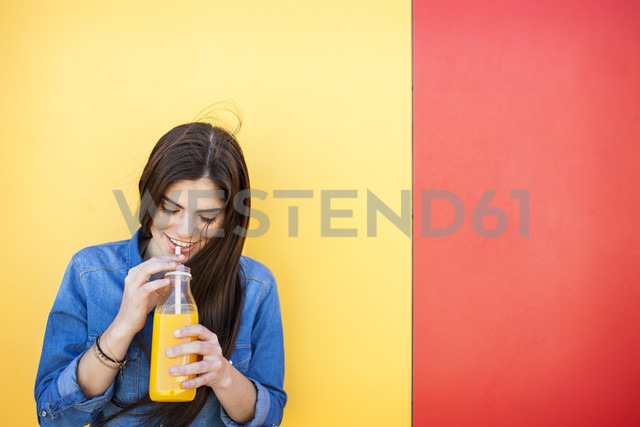 Smiling young woman in front of colourful wall drinking orange juice - VABF01288 - Valentina Barreto/Westend61