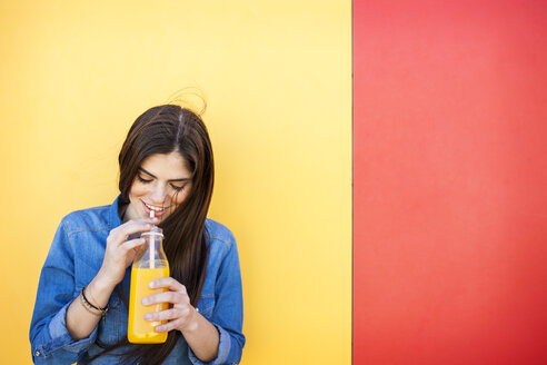 Smiling young woman in front of colourful wall drinking orange juice - VABF01288