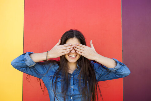 Portrait of smiling young woman in front of colourful wall covering eyes with her hands - VABF01291