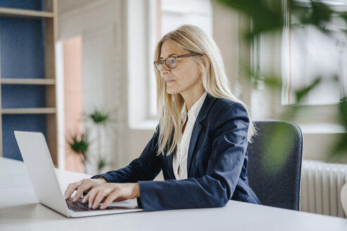 Businesswoman using laptop in office - JOSF00703