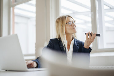 Businesswoman using laptop and cell phone in office - JOSF00706