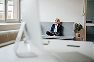 Relaxed businesswoman sitting on couch - JOSF00712