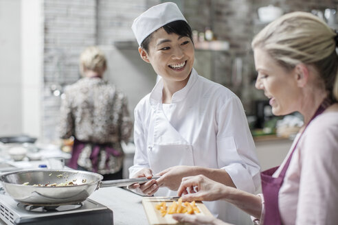 Female chef smiling at student in cooking class - ZEF13553