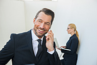 Smiling businessman on cell phone and businesswoman using laptop outdoors - CHAF01832