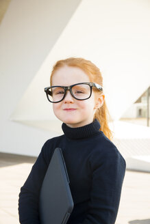 Girl wearing oversized glasses holding laptop - CHAF01835