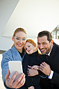 Smiling businessman and businesswoman with girl taking a selfie - CHAF01844