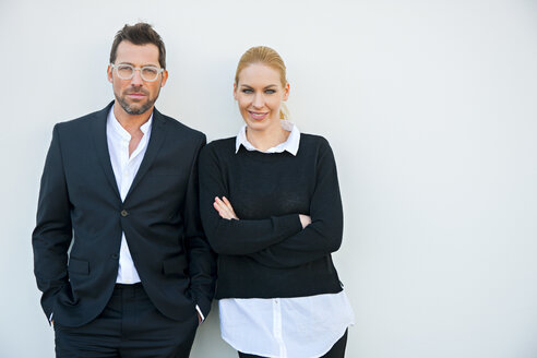 Portrait of confident businessman and woman against white wall - CHAF01865