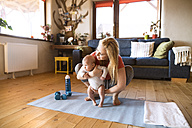 Mother with baby and dumbbells at home - HAPF01369