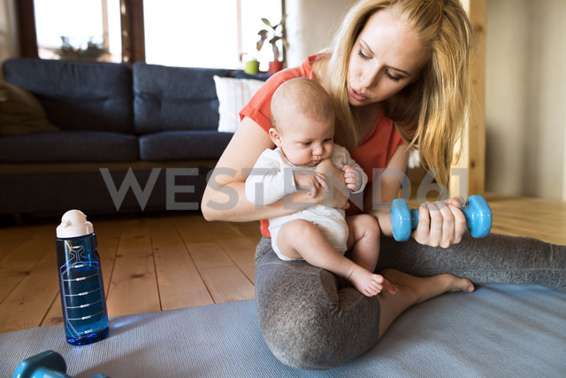 Mother with baby exercising with dumbbell at home - HAPF01372 - HalfPoint/Westend61