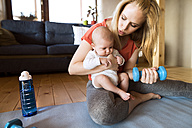 Mother with baby exercising with dumbbell at home - HAPF01372