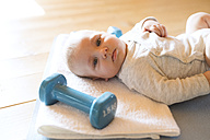 Baby at home lying on mat next to dumbbells - HAPF01375