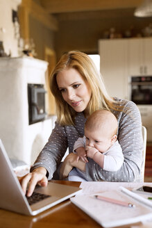 Mother with baby at home using laptop - HAPF01387