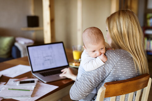 Mother with baby at home using laptop - HAPF01393