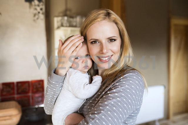 Portrait of smiling mother holding baby at home - HAPF01399