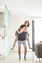 Playful young man carrying girlfriend piggyback at home - SIPF01520