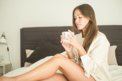 Young woman sitting on bed with cup of coffee - SIPF01535