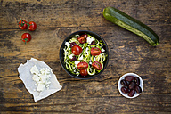 Bowl of zucchini spaghetti with feta, cherry tomatoes and black olives on wood - LVF05984