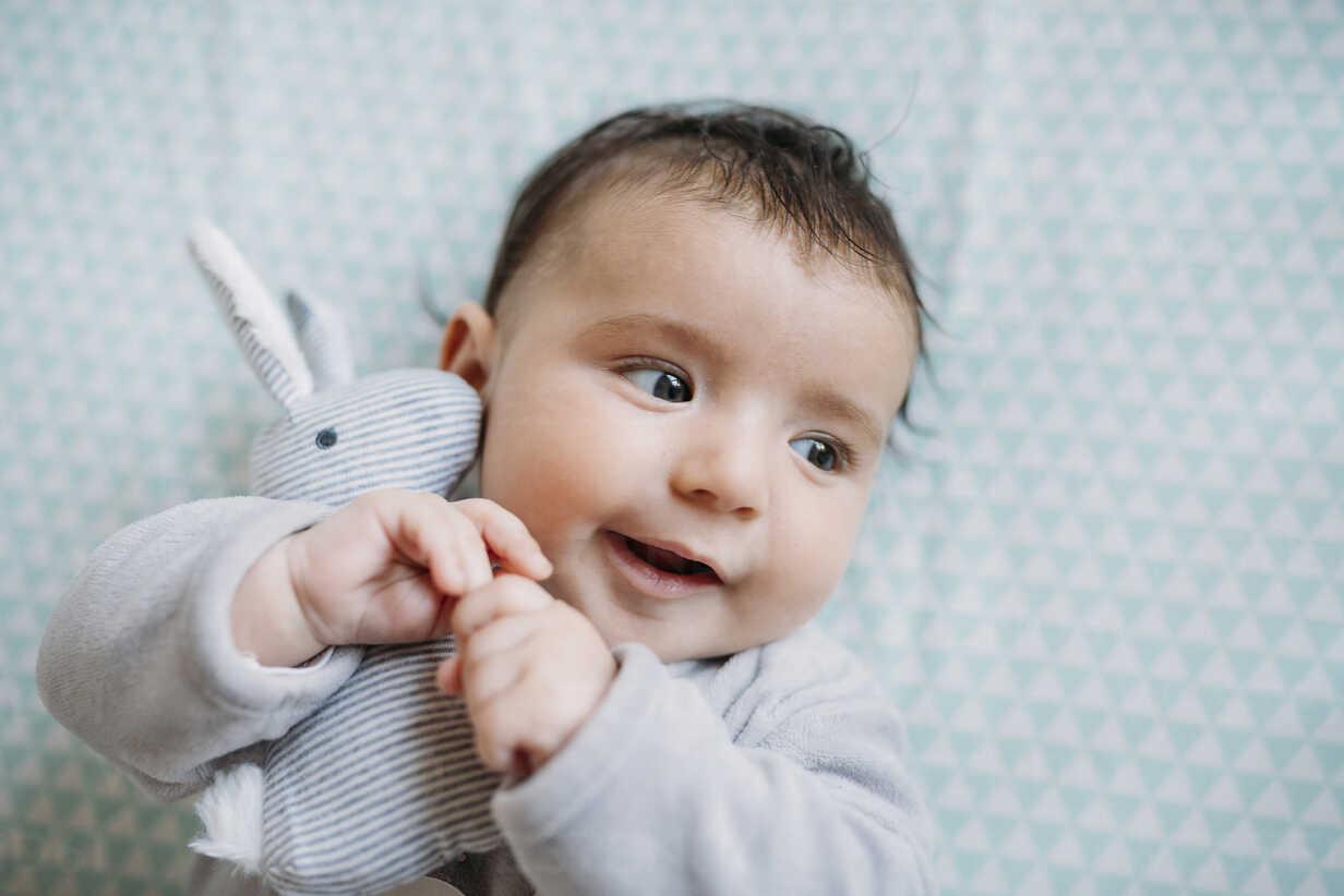 Portrait of smiling baby girl lying on bed cuddling with toy bunny - GEMF01562 - Gemma Ferrando/Westend61