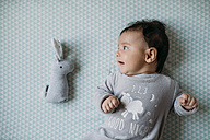 Baby girl lying on bed beside toy bunny - GEMF01565