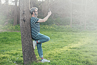 Bearded man leaning against tree trunk taking selfie with smartphone - RTBF00791