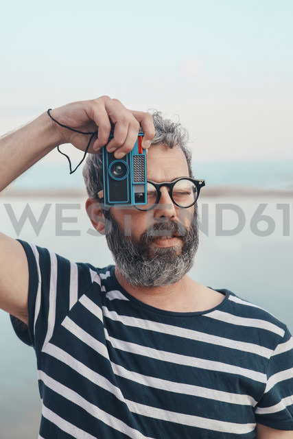 Portrait of bearded man taking photo of viewer with vintage camera - RTBF00803