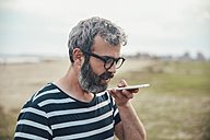 Bearded man sending voice message with smartphone on the beach - RTBF00806