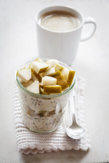 Glass of overnight oats with chia seeds, almond milk and pears - EVGF03197