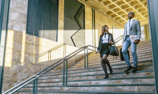 Young businessman and woman climbing stairs - DAPF00630