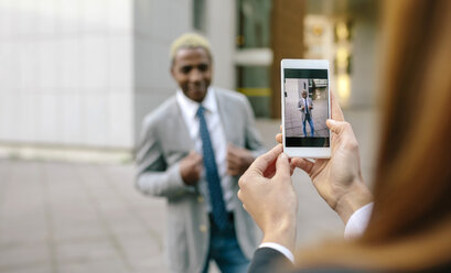 Young businessman and woman taking smart phone pictures - DAPF00633