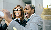 Young businessman and woman taking smart phone pictures - DAPF00636