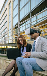 Young businessman and woman using VR goggles - DAPF00639