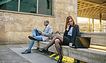 Young businessman and woman sitting on bench, woman talking on the phone - DAPF00645