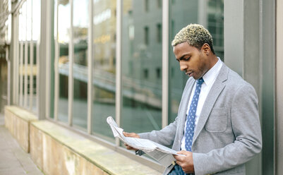 Businessman leaning against wall, reading newspaper - DAPF00648