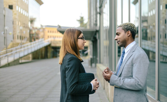 Young businessman and woman talking in front of office building - DAPF00654