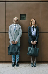 Young businessman and woman standing in front of steel wall - DAPF00666