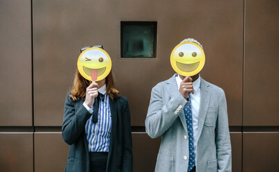 Young businessman and woman covering faces with emoji masks - DAPF00669