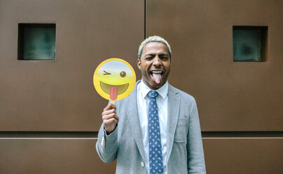 Businessman holding emoji smiling with tongue sticking out - DAPF00672