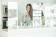 Portrait of young woman holding coffee cup with boyfriend in modern kitchen - SIPF01538