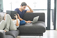 Young couple on couch relaxing with book and laptop - SIPF01550