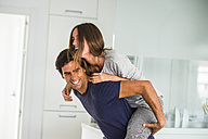 Playful young man carrying girlfriend piggyback at home - SIPF01556