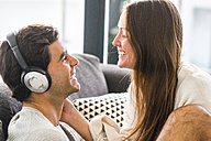 Smiling young woman looking at man wearing headphones at home - SIPF01562