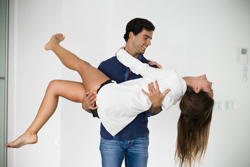 Playful young man carrying girlfriend at home - SIPF01568