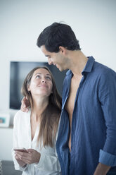 Smiling young couple in love with cell phone at home - SIPF01577