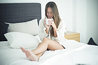 Young woman sitting on bed with cup of coffee - SIPF01586