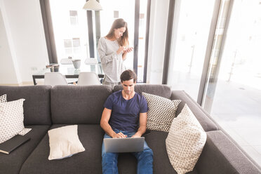 Young couple at home using cell phone and laptop - SIPF01592